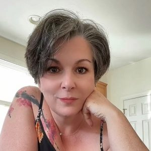 A white woman with short hair and tattoos looking at the camera