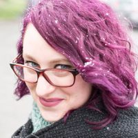 A white woman with pink hair and glasses