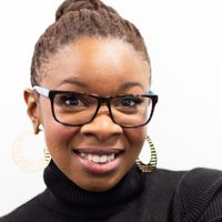 A smiling black woman with glasses and pulled-back hair looking at the camera