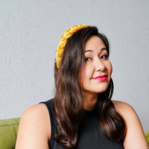 A woman with light brown skin and dark brown hair wearing a bright yellow headband