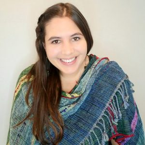 A white woman with long brown hair and a colourful shawl smiles at the camera