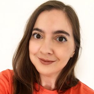 A white woman with brown hair and an orange shirt smiling at the camera