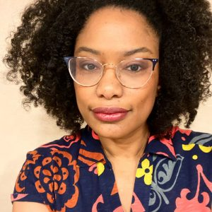 A black woman wearing glasses and a colourful shirt